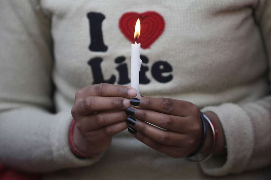 An Indian protester holds a candle during a protest demanding better security for women in New Delhi on December 29, 2012, following the death of a rape victim from the Indian capital.  Indian leaders appealed for calm and security forces headed off fresh unrest by turning New Delhi into a fortress after a student who was savagely gang-raped died in a Singapore hospital. Police threw a ring of steel around the center of the Indian capital after news of the 23-year-old medical student's death was broken in the early hours by the Singapore hospital that had been treating her for the last two days. Photo: Andrew Caballero-reynolds, AFP/Getty Images