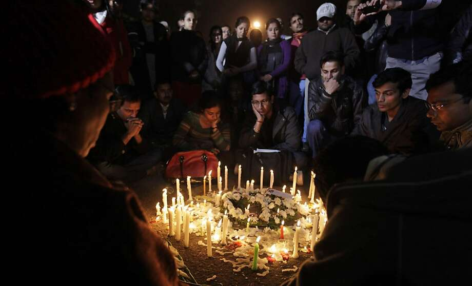 A wreath and candles are placed on a road as Indians sit around it during a gathering to mourn the death of a 23-year-old gang rape victim in New Delhi, India, Saturday, Dec. 29, 2012. Indian police charged six men with murder on Saturday, adding to accusations that they beat and gang-raped the woman on a New Delhi bus nearly two weeks ago in a case that shocked the country. The murder charges were laid after the woman died earlier Saturday in a Singapore hospital where she has been flown for treatment. Photo: Altaf Qadri, Associated Press