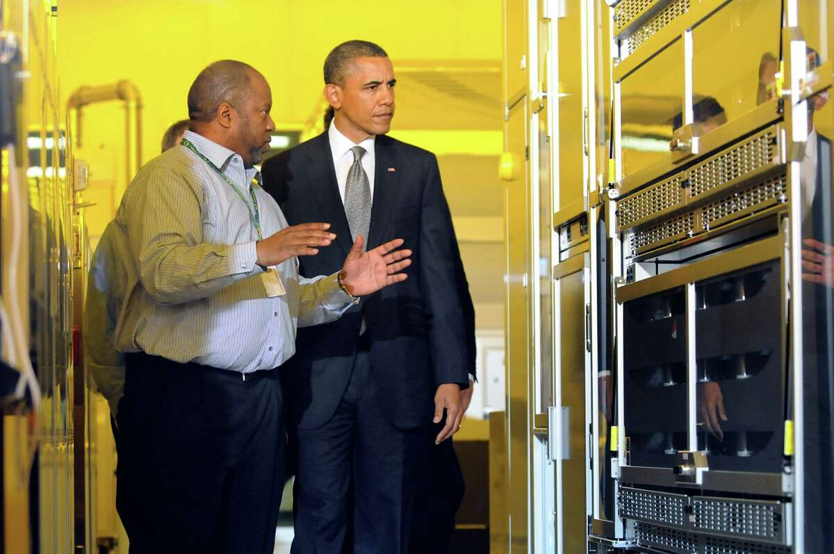 Warren Montgomery, left, CNSE assistant vice president of advanced technology and business development talks with President Barack Obama, right, as he tours a clean room on Tuesday, May 8, 2012, at University at Albany College of Nanoscale Science and Engineering in Albany, N.Y. (Cindy Schultz / Times Union)