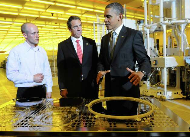Chris Borst, left, CNSE assistant vice president for module engineering, gives a tour to President Barack Obama, right, and Gov. Andrew Cuomo, center, as they view wafers in a clean room on Tuesday, May 8, 2012, at University at Albany College of Nanoscale Science and Engineering in Albany, N.Y. (Cindy Schultz / Times Union) Photo: Cindy Schultz / 00017555B
