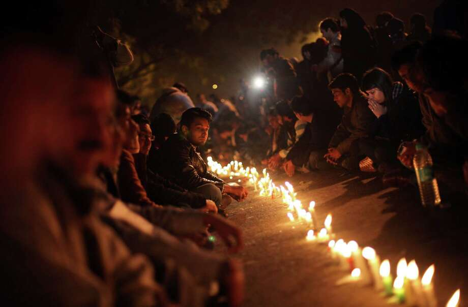 Indians participate in a candle lit vigil as they mourn the death of a gang rape victim in New Delhi, India, Saturday, Dec. 29, 2012. Indian police charged six men with murder on Saturday, adding to accusations that they beat and gang-raped the woman on a New Delhi bus nearly two weeks ago in a case that shocked the country. The murder charges were laid after the woman died earlier Saturday in a Singapore hospital where she has been flown for treatment. (AP Photo/Altaf Qadri) Photo: Altaf Qadri, STR / AP