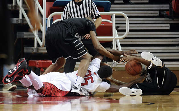 Lamar player Stan Brown, #35, scrambles for the ball with two Brooklyn Blackbirds during the Lamar University mens basketball game against Long Island University at the Montagne Center on December 29, 2012.  Lamar won over LIU 81 - 80. Photo taken: Randy Edwards/The Enterprise