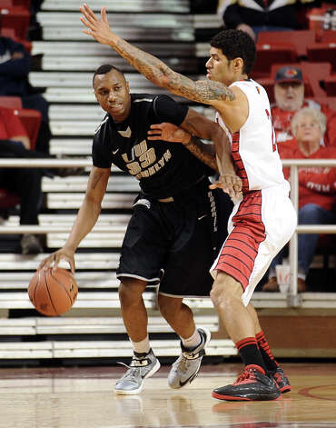 Lamar player Nikko Acosta, #2, guards LIU player E.J. Reed, #33, during the Lamar University mens basketball game against Long Island University at the Montagne Center on December 29, 2012.  Lamar won over LIU 81 - 80. Photo taken: Randy Edwards/The Enterprise