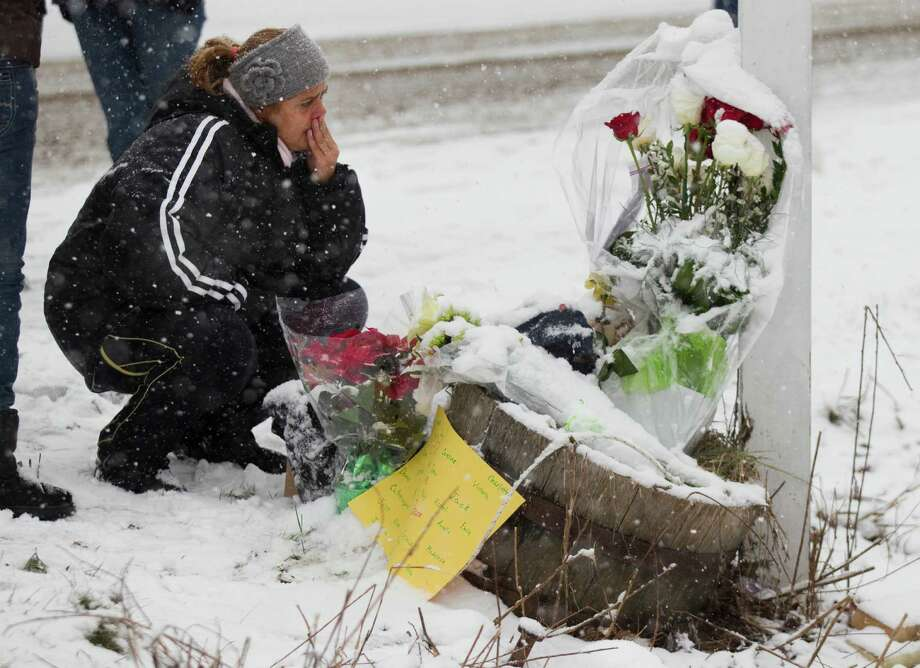 Carmen Faria, of Miami, kneels Saturday at the site where a makeshift memorial once stood near Sandy Hook Elementary School. Two of the main memorials have been taken down, leaving just a few items left at the site. Photo: Brett Coomer, Staff Photographer / The News-Times