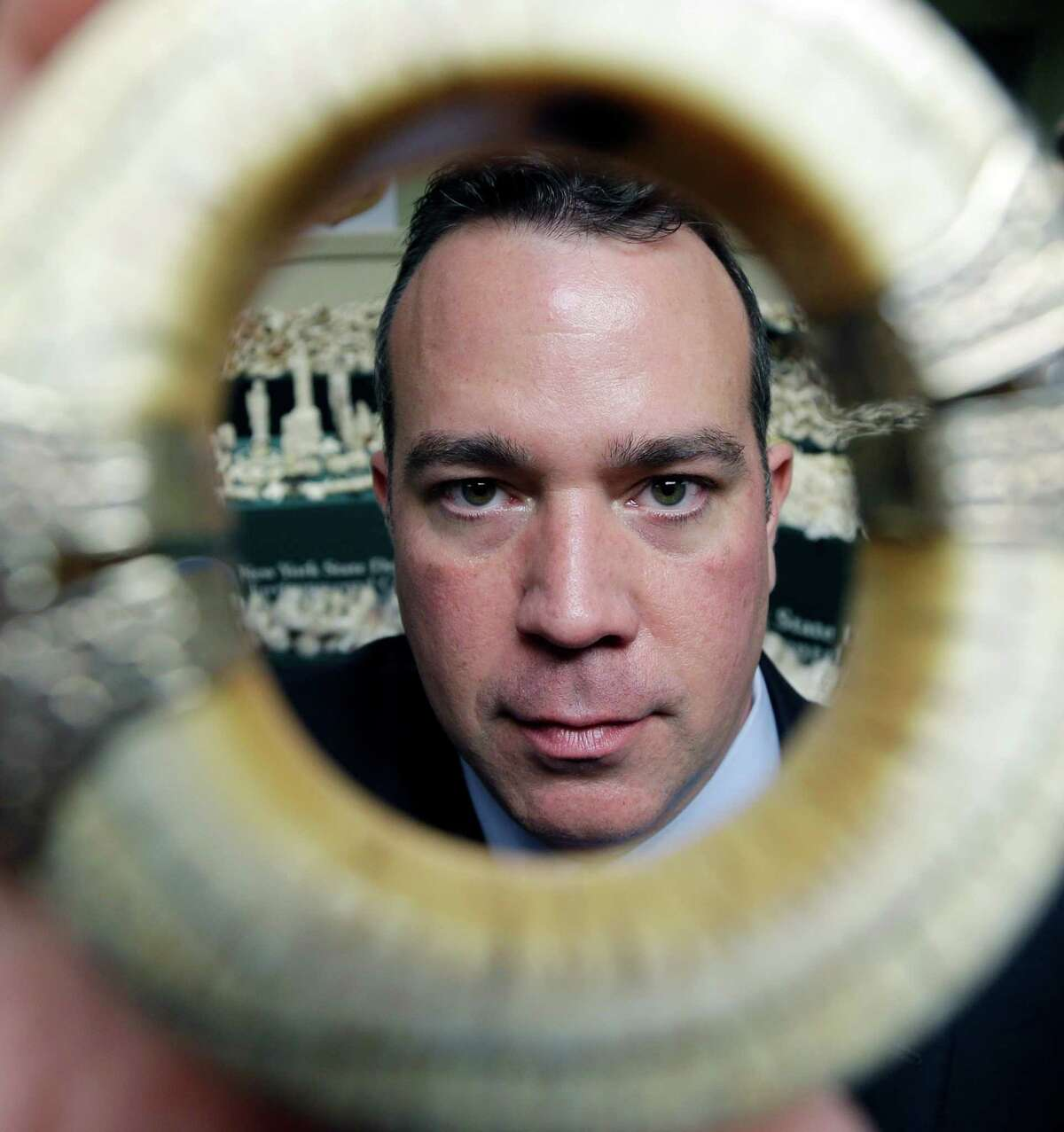 In this Dec. 14, 2012 photo, Lt. John Fitzpatrick, an investigator with the New York State Department of Environmental Conservation, shows off an ivory bracelet in Albany, N.Y. In an effort to shutter the U.S. as a modern elephant graveyard, investigators recently confiscated two tons of ivory that was for sale or passed through New York City, a primary black market for the ongoing African slaughter of the world?'s largest land mammals. (AP Photo/Mike Groll)
