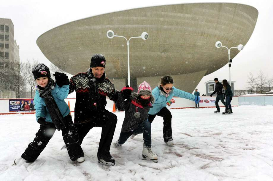 Paul Wylie, 1992 Olympic Silver Medalist, second from left joins young fans in a group glide on a snowy ice rink on Saturday, Dec. 29, 2012, at the Empire State Plaza in Albany, N.Y. Joining Wylie, from left, are Kaileigh Tricarick, 8, of Waterford, Maggie Partlow, 9, of Halfmoon and her sister Virginia, 11. Wylie's visit was sponsored by Starlight Children's Foundation and Hannaford Supermarkets. (Cindy Schultz / Times Union) Photo: Cindy Schultz / 00020590A