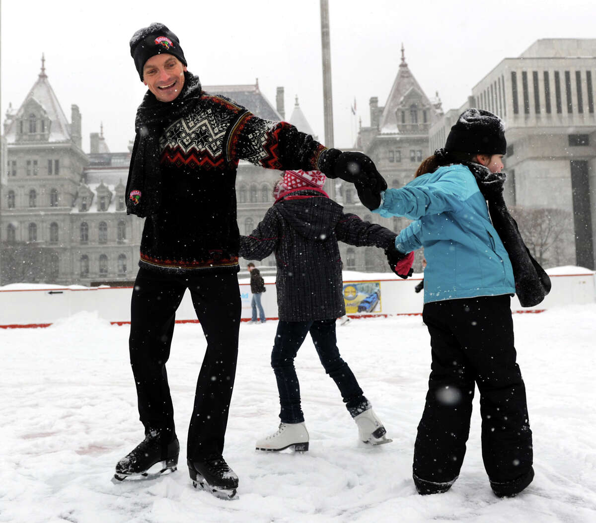 Paul Wylie, 1992 Olympic Silver Medalist, left, joins young fans in a friendship circle on the snowy ice rink on Saturday, Dec. 29, 2012, at the Empire State Plaza in Albany, N.Y. Joining Wylie are Kaileigh Tricarick, 8, of Waterford, right, and Maggie Partlow, 9, of Halfmoon. Wylie's visit was sponsored by Starlight Children's Foundation and Hannaford Supermarkets. (Cindy Schultz / Times Union)