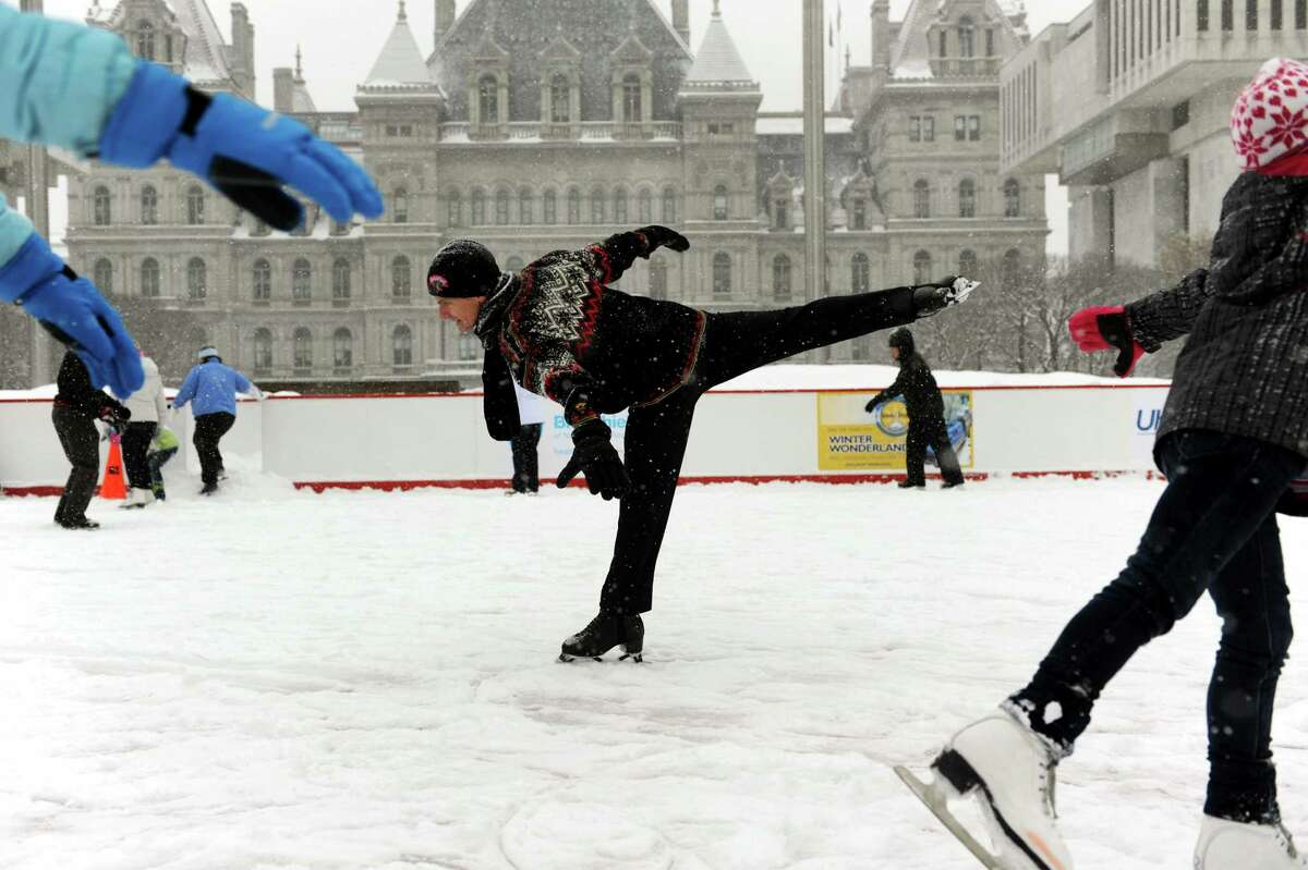Paul Wylie, 1992 Olympic Silver Medalist, center, glides through the snow on the ice rink on Saturday, Dec. 29, 2012, at the Empire State Plaza in Albany, N.Y. Wylie's visit was sponsored by Starlight Children's Foundation and Hannaford Supermarkets. (Cindy Schultz / Times Union)