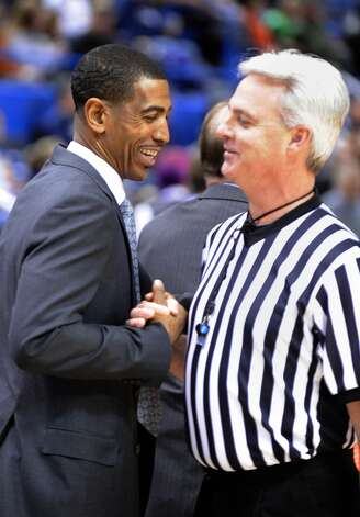 UConn coach Kevin Ollie, left, greets an official before the start of his team's NCAA college basketball game against Washington in Hartford, Conn., Saturday, Dec. 29, 2012. Earlier in the afternoon UConn officials announced that Ollie had been awarded a new multi-year contract. (AP Photo/Fred Beckham)