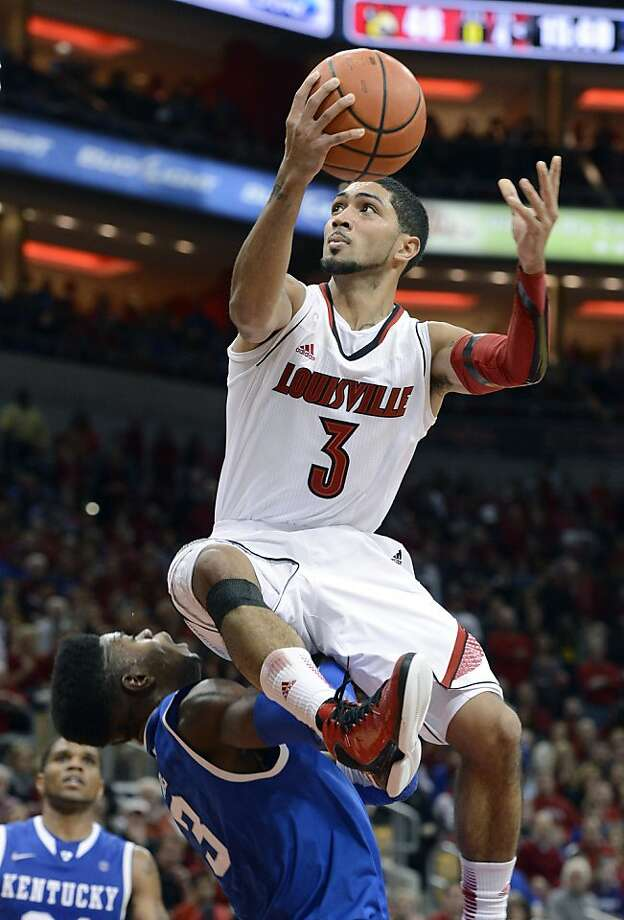 Peyton Siva (right) goes over Nerlins Noel for a layup as Louisville built a 17-point, second-half lead before Kentucky rallied. Photo: Timothy D. Easley, Associated Press