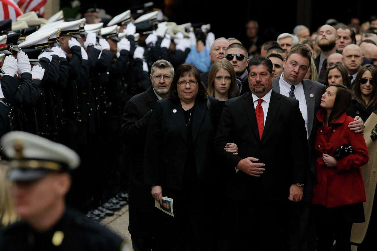 Mitzie Norman, center left, widow of slain Bellaire Police Sgt. Jimmie Norman, is escorted by funeral director, Terry Loving, as they lead procession with Norman's father, James Norman, shown in next row left, daughter, Dallas Norman, along with her brother, Daniel Norman, and his wife, Hillary Norman, right, after funeral service at Houston First Baptist Church.