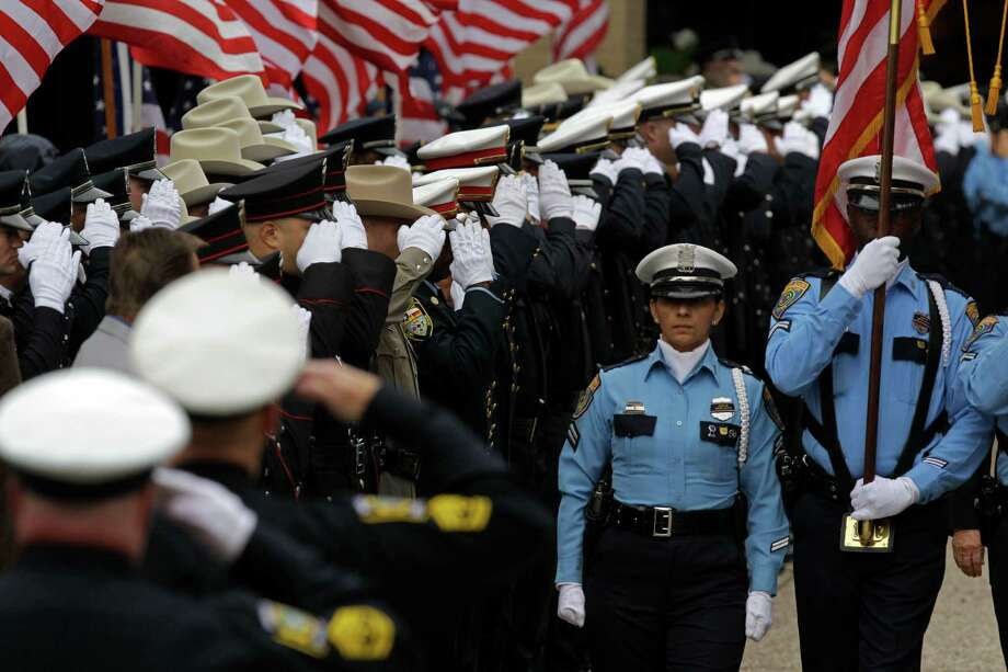 Police officers salute as the honor guard leads the procession from the  funeral service for Bellaire Police Sgt. Jimmie Norman at Houston First Baptist Church. Photo: Melissa Phillip, Houston Chronicle / © 2012 Houston Chronicle
