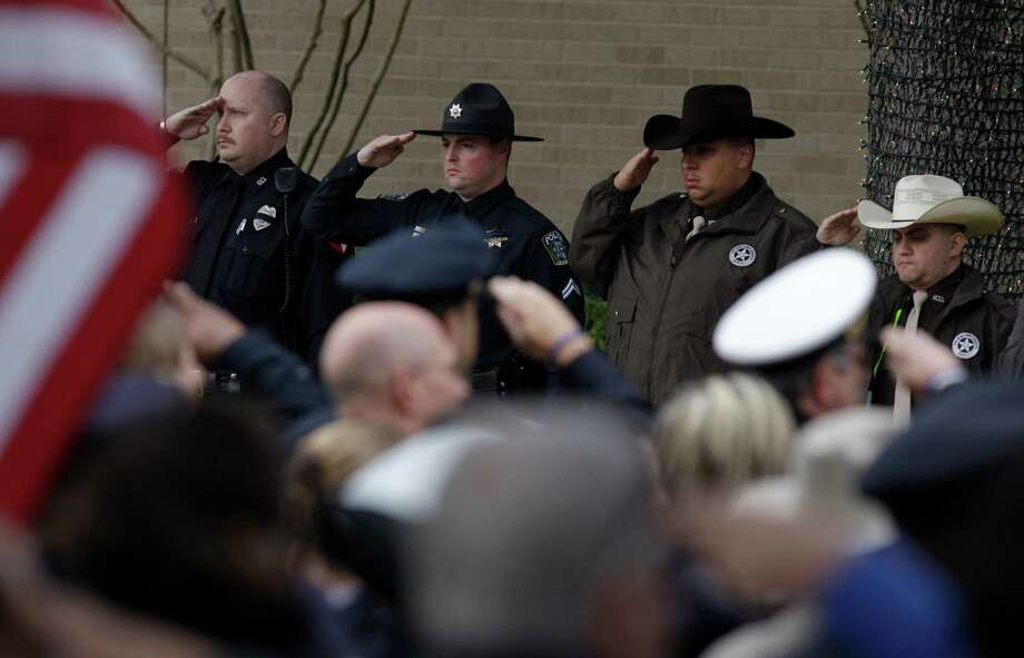 Police officers salute as the casket is taken to hearse after funeral service for Bellaire Police Sgt. Jimmie Norman at Houston First Baptist Church. Photo: Melissa Phillip, Houston Chronicle / © 2012 Houston Chronicle