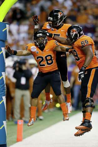 Oregon State's Terron Ward (28) celebrates with teammates Josh Andrews (69) and Oregon State's Brandin Cooks, center, after he scored a touchdown in the second quarter of the Alamo Bowl NCAA football game against Texas, Saturday, Dec. 29, 2012, in San Antonio.  (AP Photo/Eric Gay) Photo: Eric Gay, Associated Press / AP