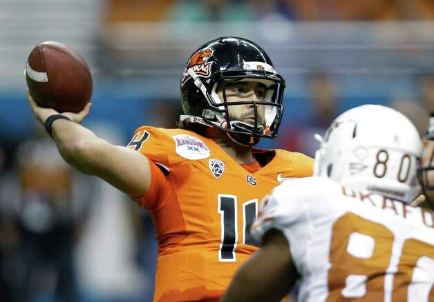 Oregon State's Jordan Poyer, left, throws as Texas defender Alex Okafor (80) pressures him during the second quarter of the Alamo Bowl NCAA football game, Saturday, Dec. 29, 2012, in San Antonio.  (AP Photo/Eric Gay) Photo: Eric Gay, Associated Press / AP