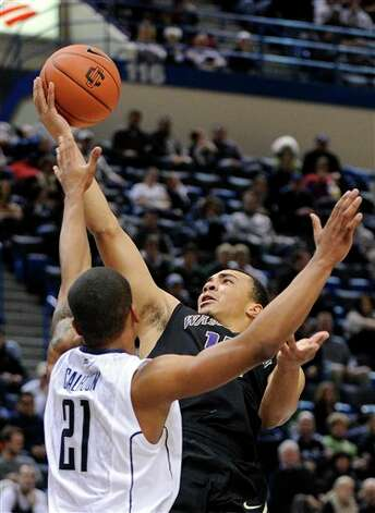 UConn's DeAndre Daniels, left, defends Washington's Andrew Andrews during the first half of an NCAA college basketball game in Hartford, Conn., Saturday, Dec. 29, 2012. (AP Photo/Fred Beckham)