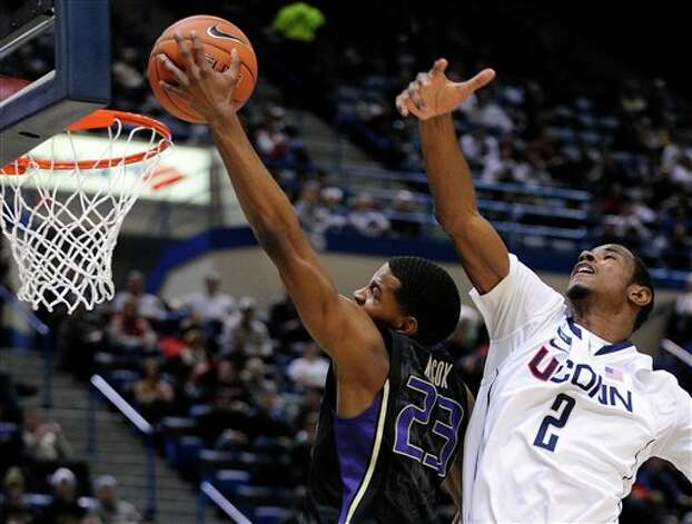 Washington's C.J. Wilcox, left, drives past UConn's DeAndre Daniels during the first half of an NCAA college basketball game in Hartford, Conn., Saturday, Dec. 29, 2012. (AP Photo/Fred Beckham)