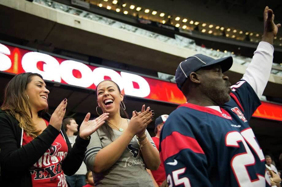 Thanks to the Texans' successful season and the play of her Pro Bowl husband Duane Brown, Devi Brown, center, is usually all smiles while watching home games. Photo: Smiley N. Pool, Staff / © 2012  Houston Chronicle