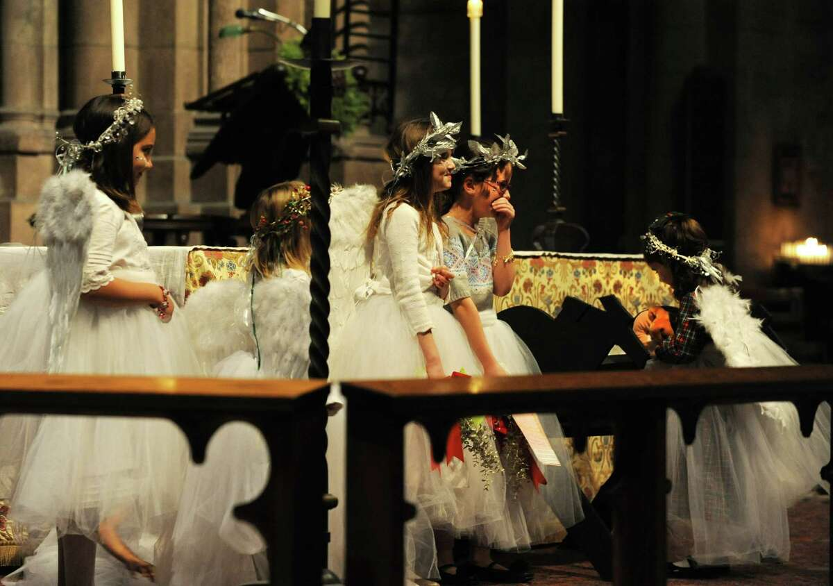 Students from the Sunday School Program dressed as angels giggle as Maddy Tyler unexpectedly places her stuffed monkey in Baby Jesus's crib during an early Christmas Eve mass at The Cathedral of All Saints on South Swan St. on Monday Dec. 24, 2012 in Albany, N.Y. Maddy had her stuffed monkey with her because she wasn't feeling well. (Lori Van Buren / Times Union)