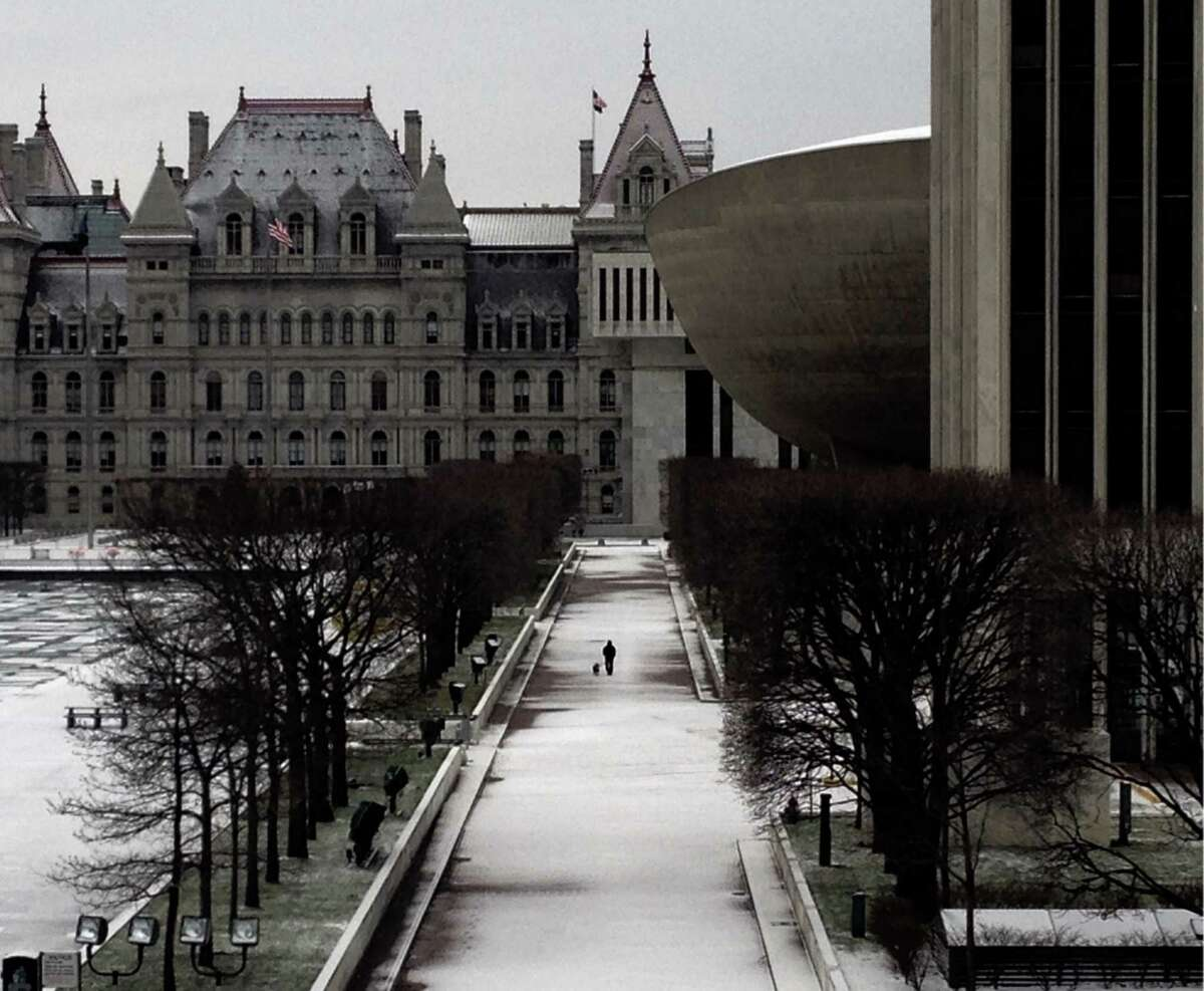 A woman walks her dog through a snow covered Empire State Plaza on Sunday morning, Dec. 25, 2012 in Albany, NY.
