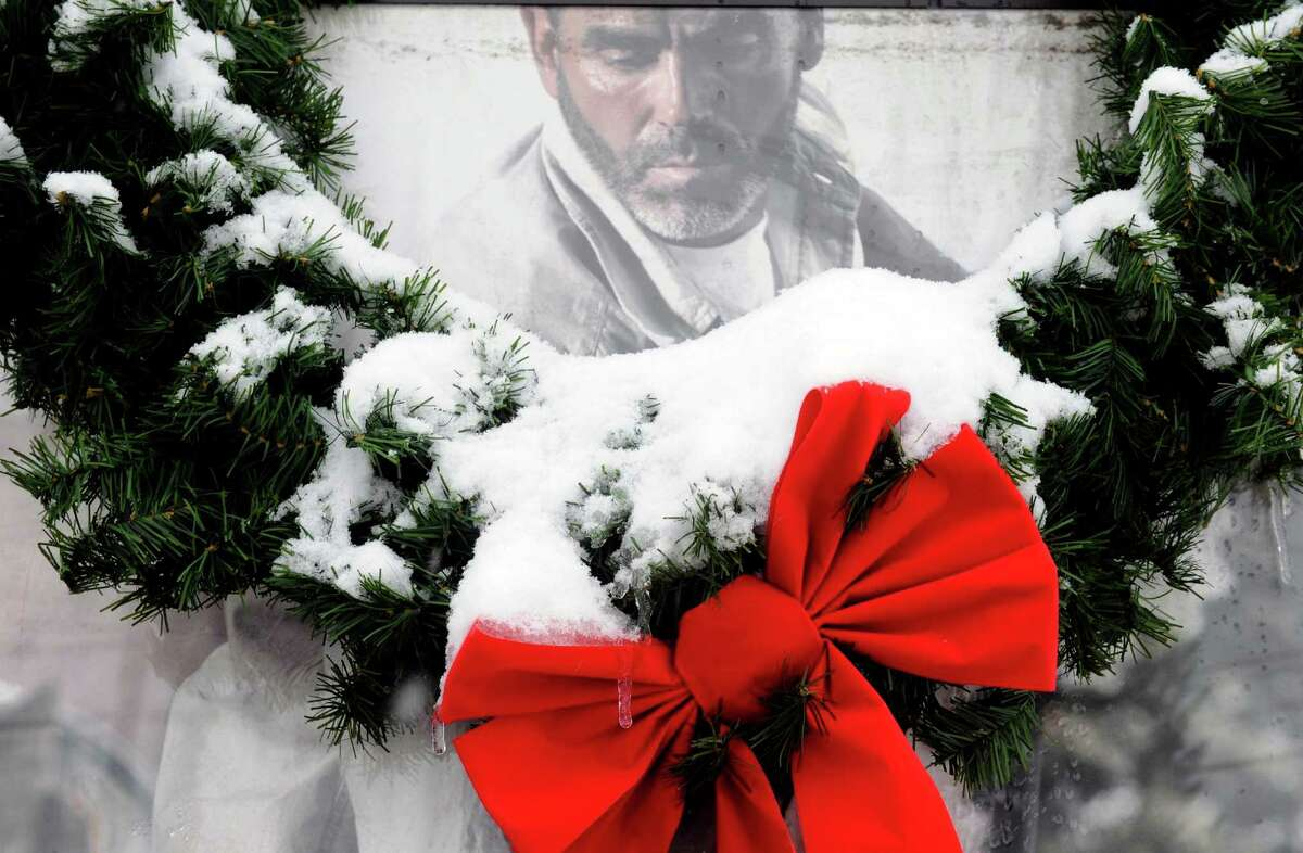 A snow covered wreath hangs in front of a Carhartt clothing advertisement at Phillips Hardware in Colonie, N.Y., Thursday Dec. 27 2012. (Michael P. Farrell/Times Union)