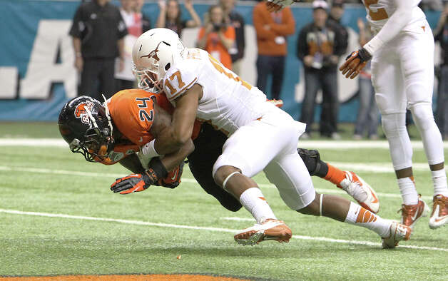 Oregon State's Cyril Noland-Lewis (24) drives in for a touchdown against Texas' Adrian Phillips (17) in the first half of the Valero Alamo Bowl on Saturday, Dec. 29, 2012. Photo: Kin Man Hui, Express-News / © 2012 San Antonio Express-News