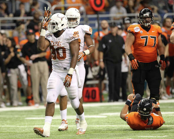 Texas' Alex Okafor (80) gestures after sacking Oregon State quarterback Cody Vaz (14) in the first half of the Valero Alamo Bowl on Saturday, Dec. 29, 2012. Photo: Kin Man Hui, Express-News / © 2012 San Antonio Express-News