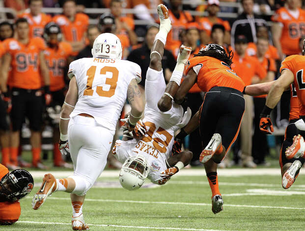 Texas' D. J. Monroe (26) gets flipped over while returning a kick against Oregon State's Anthony Watkins (03) in the first half of the Valero Alamo Bowl on Saturday, Dec. 29, 2012. Photo: Kin Man Hui, Express-News / © 2012 San Antonio Express-News