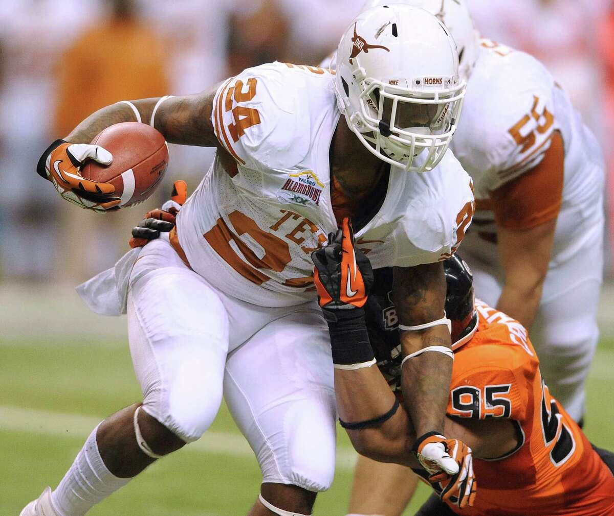 Texas running back Joe Bergeron is dragged down by his shirt collar by Oregon State defender Scott Crichton (95) during Valero Alamo Bowl action in the Alamodome on Saturday, Dec. 29, 2012.