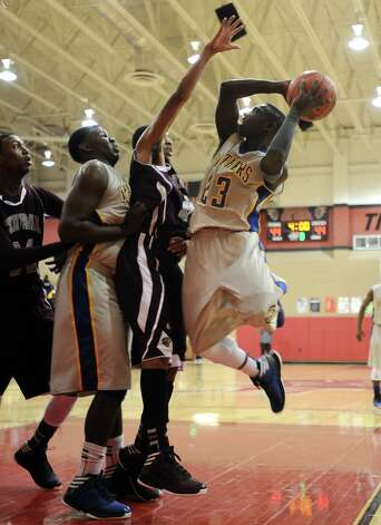 Ozen player Jordan Hunter, #23, puts it up for two during the Central High School Jaguars basketball game against the Ozen High School Panthers on Saturday, December 29, 2012, at the James Gamble Boys Basketball Tournament championship game held at Port Arthur Memorial High School. Central won over Ozen 76- 73. Photo taken: Randy Edwards/The Enterprise