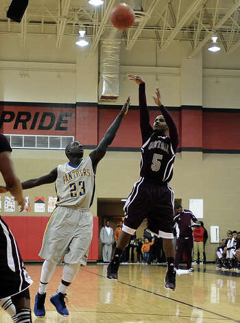 Central player Jacory Guillory, #5,puts it up for two during the Central High School Jaguars basketball game against the Ozen High School Panthers on Saturday, December 29, 2012, at the James Gamble Boys Basketball Tournament championship game held at Port Arthur Memorial High School. Central won over Ozen 76- 73. Photo taken: Randy Edwards/The Enterprise