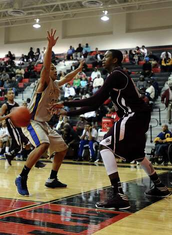 Central player E'Torrion Wilridge, #24, passes it around Ozen player Charleton Brydson, #30, during the Central High School Jaguars basketball game against the Ozen High School Panthers on Saturday, December 29, 2012, at the James Gamble Boys Basketball Tournament championship game held at Port Arthur Memorial High School. Central won over Ozen 76- 73. Photo taken: Randy Edwards/The Enterprise