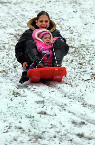 Yamilet Berrios, of Bridgeport, takes a ride on a sled with her daughter Yarielis, 2, who didn't seem to enjoy the trip down the hill as much as her mom while at Beardsley Park in Bridgeport, Conn. on Saturday December 29, 2012. Photo: Christian Abraham / Connecticut Post