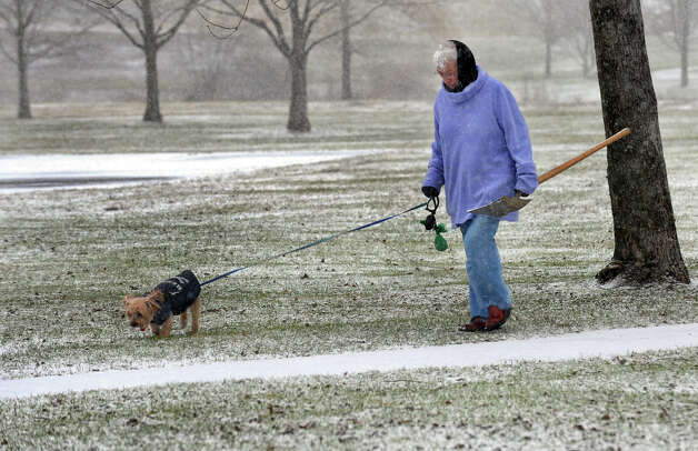 Marlene, of Trumbull, takes a stroll with her dog Spencer through Veterans Park in Trumbull, Conn. on Saturday December 29, 2012. And, no, the shovel wasn't for Spencer. Marlene, who wished to not give her last name, found the shovel on her walk and though it might belong to the town. She said she was taking it home and would call the town about it. Photo: Christian Abraham / Connecticut Post