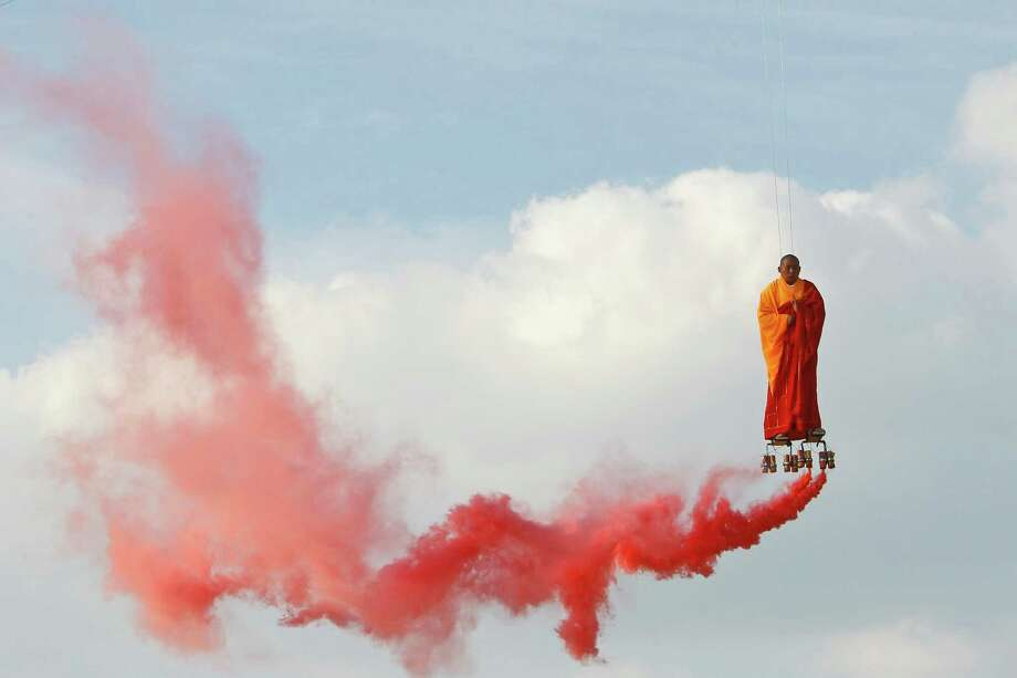 In this March 20, 2012 file photo, suspended by wires, Chinese artist Li Wei performs in the sky  at La Villette in Paris. Wei's work often depicts him in apparently gravity-defying situations. Photo: Francois Mori, ASSOCIATED PRESS / A2012