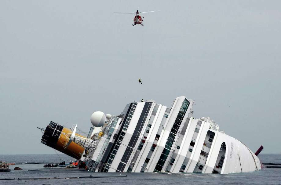 This Jan. 31, 2012 file photo shows an Italian firefighter being lowered from a helicopter onto the grounded cruise ship Costa Concordia off the Tuscan island of Giglio, Italy. Despite legal obstacles that might force them to sue in Italy, hundreds of Costa Concordia passengers and up to 1,000 businesses on the island where the capsized cruise ship ran aground are pressing ahead with U.S. lawsuits seeking millions of dollars in damages from Miami-based Carnival Corp. Photo: Pier Paolo Cito, ASSOCIATED PRESS / A2012