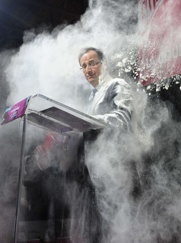 "In this Feb. 1, 2012 file photo, an unidentified woman throws flour on French Socialist Party candidate for the 2012 presidential elections, Francois Hollande, in Paris. The woman ran to the side of the podium where Hollande stood to sign a ""social contract"" in favor of housing for all. Photo: SZG, ASSOCIATED PRESS / A2012"