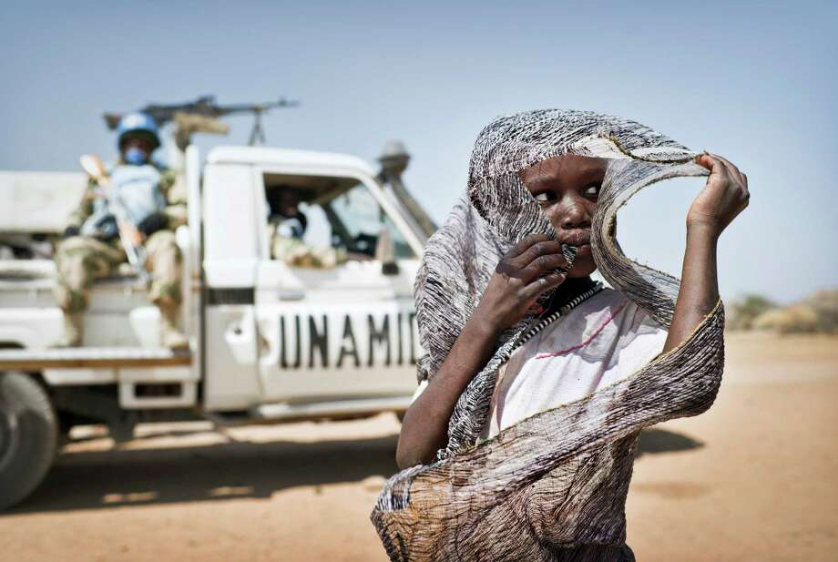 A girl and UNAMID peacekeepers in Nyoro, Sudan, Feb. 4, 2012. More than 100,000 people in Darfur have left the camps where they had taken refuge for nearly a decade and headed home to their villages over the past year, the biggest return of displaced people since the war began in 2003. Photo: SVEN TORFINN, NYT / NYTNS