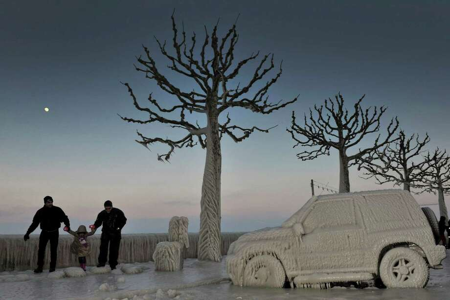 In this Feb. 5, 2012 file photo, people walk along an icy promenade past ice covered cars and trees on the shores of Lake Geneva in Versoix, Switzerland. Across Eastern Europe, thousands of people dug out from heavy snow that had fallen during a cold snap and killed hundreds of people. Photo: Martial Trezzini, ASSOCIATED PRESS / A2012