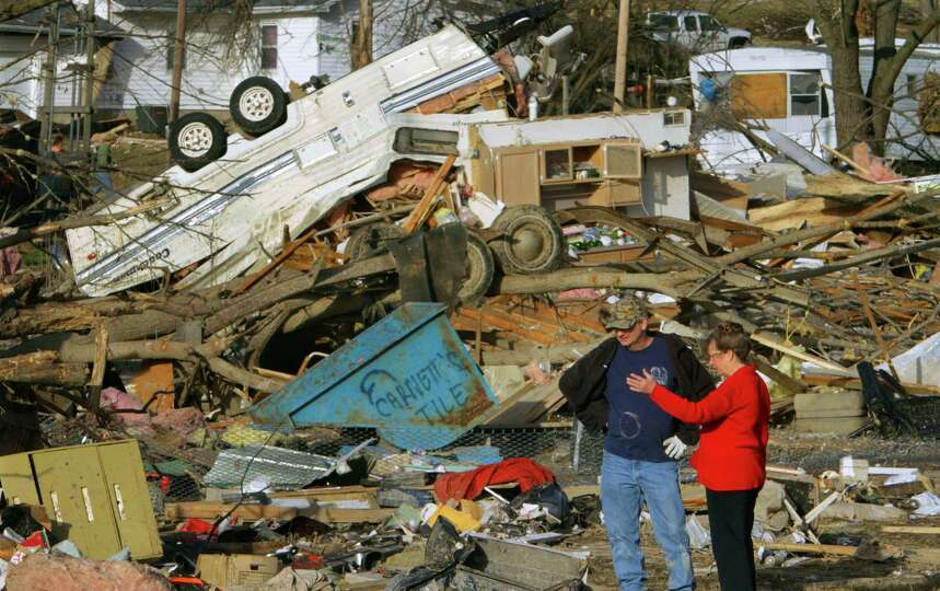 People try to salvage what they can after a tornado destroyed homes in their neighborhood Wednesday,