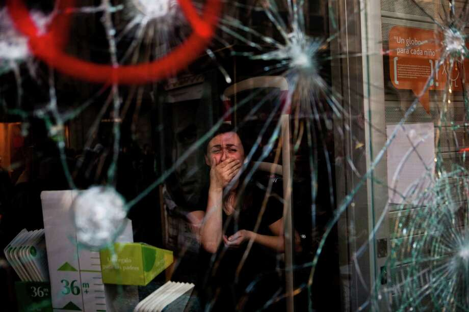 In this March 29, 2012 file photo, Mireia Arnau, 39, reacts behind the broken glass of her shop stormed by demonstrators during clashes at the general strike in Barcelona. Spanish workers livid over labor reforms they see as flagrantly pro-business staged a nationwide strike and tried to bring the country to a halt by blocking traffic, closing factories and clashing with police in rowdy demonstrations. Photo: EMILIO MORENATTI, ASSOCIATED PRESS / AP2012