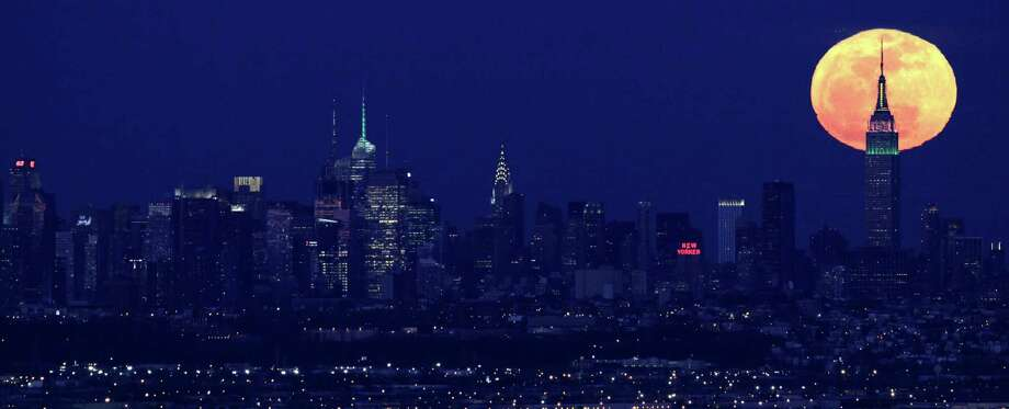 A full moon rises behind the Empire State Building in New York in this view from Eagle Rock Reservation in West Orange, N.J., on Friday, April 6, 2012. Photo: Julio Cortez, ASSOCIATED PRESS / AP2012