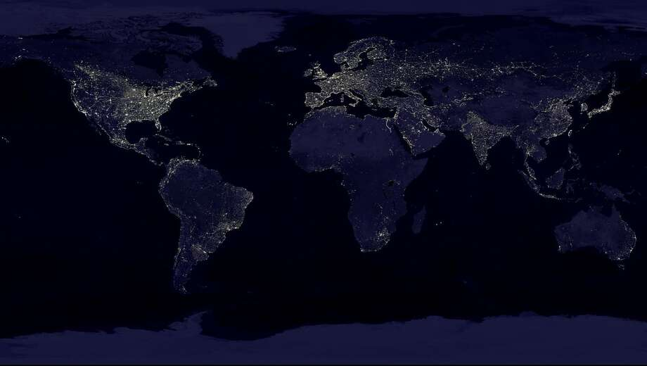 "This NASA image from a composite assembled from data acquired by the Suomi NPP satellite in April and October 2012 shows the earth's city lights at night. It took 312 orbits to get a clear shot of every parcel of Earth's land surface and islands at night.The new data was mapped over existing Blue Marble imagery of Earth to provide a realistic view of the planet. The image was made possible by the new satellite's ""day-night band"" of the Visible Infrared Imaging Radiometer Suite (VIIRS), which detects light in a range of wavelengths from green to near-infrared and uses filtering techniques to observe dim signals such as city lights, gas flares, auroras, wildfires, and reflected moonlight. Photo: Uncredited, ASSOCIATED PRESS / AP2012"