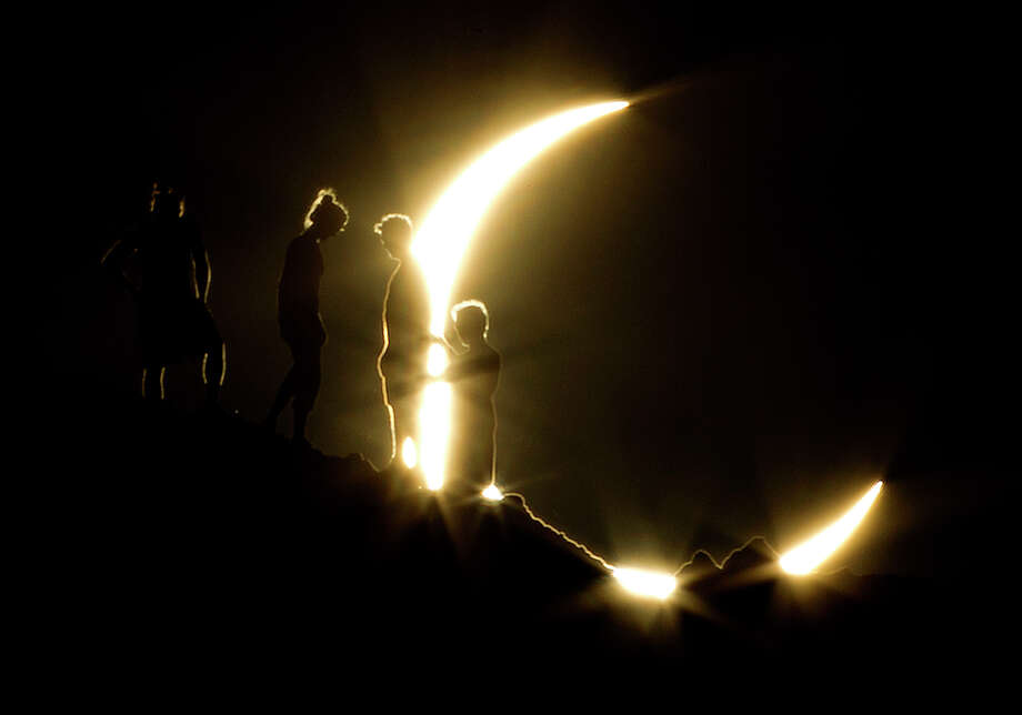 In this May 20, 2012 file photo, hikers watch an annular eclipse from Papago Park in Phoenix. The annular eclipse, in which the moon passes in front of the sun leaving only a golden ring around its edges, was visible to wide areas across China, Japan and elsewhere in the region before moving across the Pacific to be seen in parts of the western United States. Photo: Michael Chow, ASSOCIATED PRESS / A2012