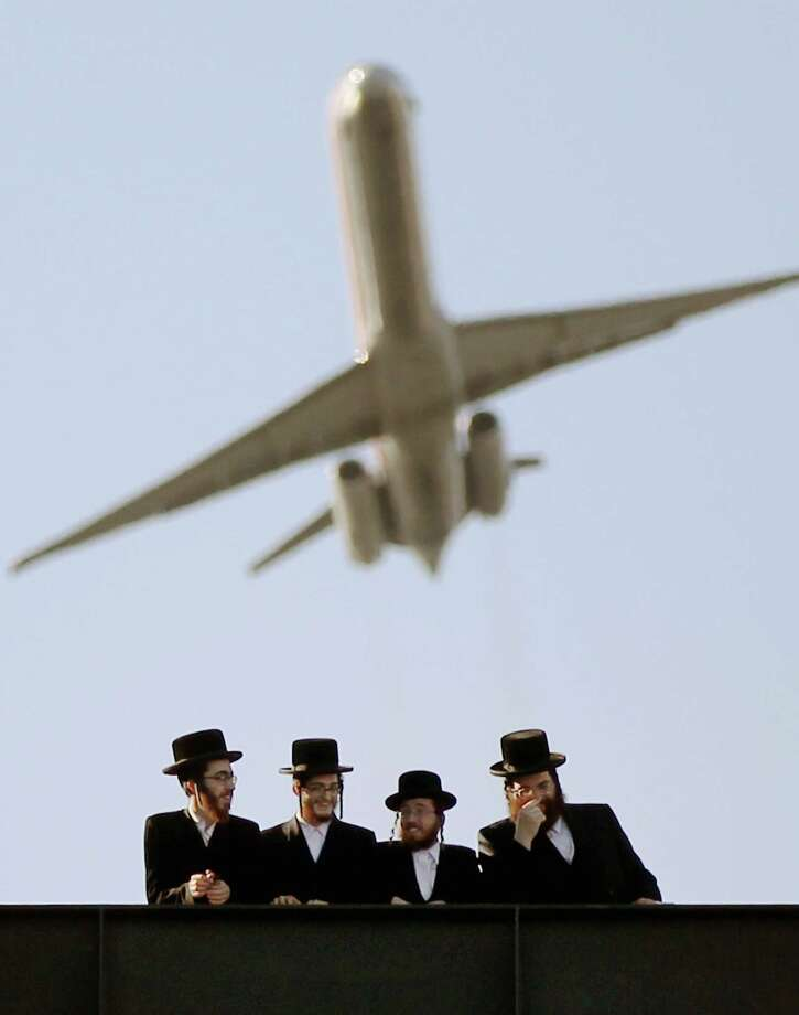 Ultra-Orthodox Jews gather at Citi Field as a plane takes off overhead from LaGuradia Airport at a meeting to discuss the risks of using the Internet on May 20, 2012 in the Queens borough of New York City. More than 40,000 were expected to attend the rally at Citi Field, the home of the New York Mets, which organizers said would promote religiously responsible ways to use the Internet. Photo: Mario Tama, Getty Images / 2012 Getty Images