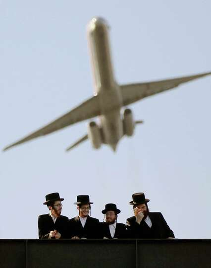 Ultra-Orthodox Jews gather at Citi Field as a plane takes off overhead from LaGuradia Airport at a m