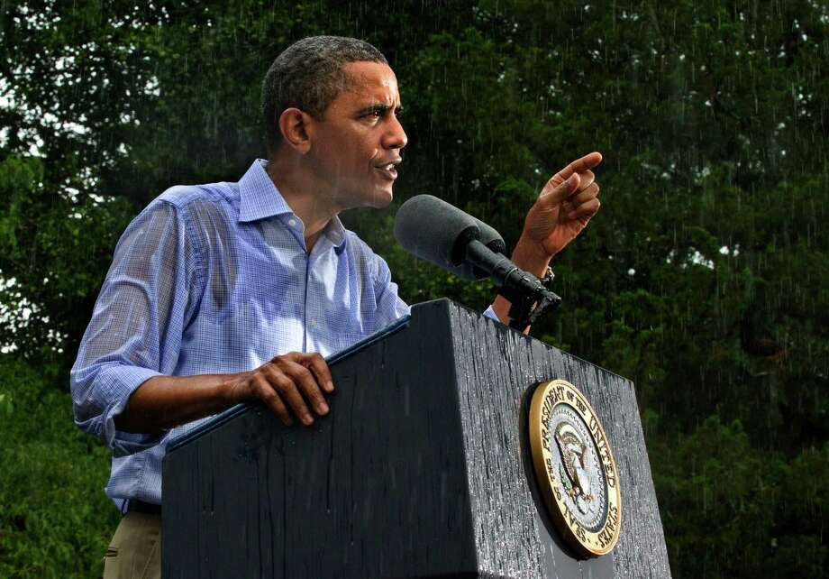 In this July 14, 2012 file photo, President Barack Obama campaigns for re-election in the heavy rain at Walkerton Tavern & Gardens in Glen Allen, Va., near Richmond. Photo: J. Scott Applewhite, ASSOCIATED PRESS / The Associated Press2012