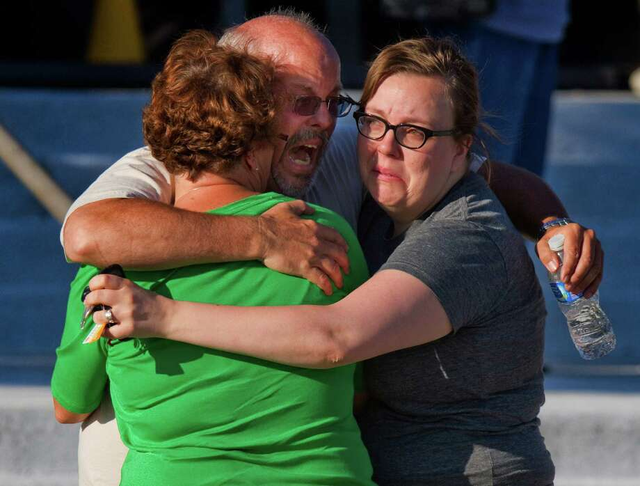 """In this July 20, 2012 file photo, Tom Sullivan, center, embraces family members outside Gateway High School where he had been searching franticly for his son Alex Sullivan who celebrated his 27th birthday by going to see """"The Dark Knight Rises,"""" movie where a gunman opened fire in Aurora, Colo. Photo: Barry Gutierrez, ASSOCIATED PRESS / The Associated Press2012"""