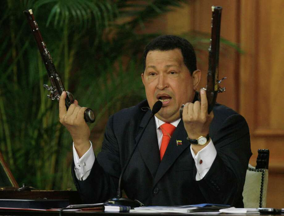 In this July 24, 2012 file photo, Venezuela's President Hugo Chavez holds up a pair of pistols that he says belonged to Venezuela's independence hero Simon Bolivar during a ceremony marking 229th anniversary of Bolivar's birth at Miraflores presidential palace in Caracas, Venezuela.  Bolivar is the namesake of Chavez's Bolivarian Revolution movement, and his government is putting the finishing touches on a new mausoleum to house Bolivar's remains. Photo: Fernando Llano, ASSOCIATED PRESS / AP2012