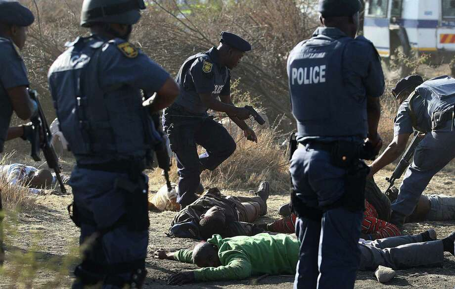 In this Aug. 16, 2012 file photo, police surround the bodies of striking miners after opening fire on a crowd at the Lonmin Platinum Mine near Rustenburg, South Africa. South African police opened fire on a crowd of striking workers at a platinum mine, leaving an unknown number of people injured and possibly dead. Motionless bodies lay on the ground in pools of blood. Photo: STR, ASSOCIATED PRESS / A2012